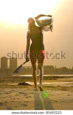 Young girl walking with kayak on her shoulder at the sunset.