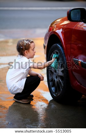 Young girl washing the wheel of a red car