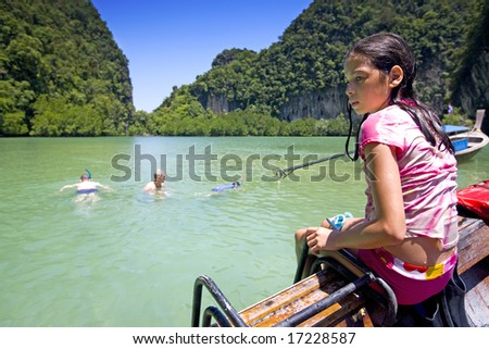 Young girl watches family swimming in beautiful lagoon in Krabi, Thailand