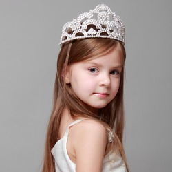 Young girl wearing a crown and a white dress with a cute smile on Holiday