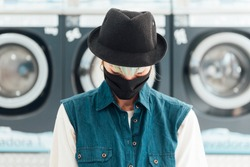 young girl wearing a hat and mask to cope with the coronavirus. She is in a public laundry, in the new normal and crestfallen, sad and tired with the washing machines in the background.