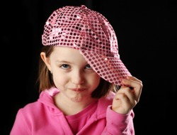 Young girl wearing a pink sequin baseball cap rolling her eyes with attitude, on black background