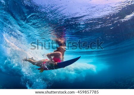 Stock Photo Young girl wearing bikini in action - surfer with surf board dive underwater under ocean wave. Family lifestyle, people water sport adventure camp and beach extreme swim on summer vacation with child.