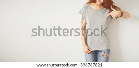Young girl wearing grey blank t-shirt and blue jeans. Concrete wall background with copy space for your text message or promotional content