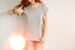 Young girl wearing grey blank t-shirt and blue jeans. Concrete white wall background, flare light