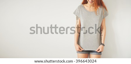 Young girl wearing grey blank t-shirt and blue jeans shorts. Concrete wall background with copy space for your text message or promotional content