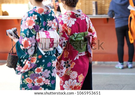 """Young girl wearing Japanese kimono standing in front of Sensoji Temple in Tokyo, Japan. Kimono is a Japanese traditional garment. The word """"kimono"""", which actually means a """"thing to wear"""" - Shutterstock ID 1065953651"""