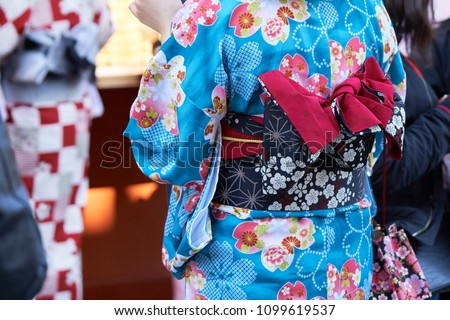 """Young girl wearing Japanese kimono standing in front of Sensoji Temple in Tokyo, Japan. Kimono is a Japanese traditional garment. The word """"kimono"""", which actually means a """"thing to wear"""" - Shutterstock ID 1099619537"""