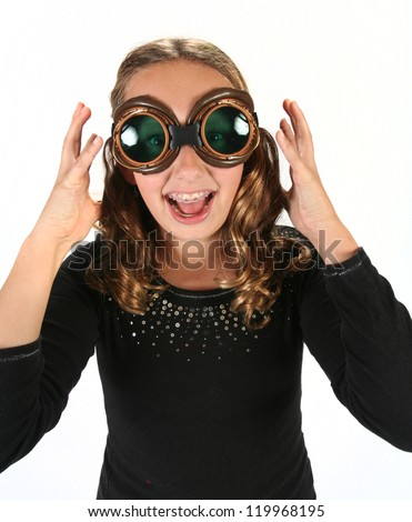 Young girl wearing steam punk goggles posing and screaming