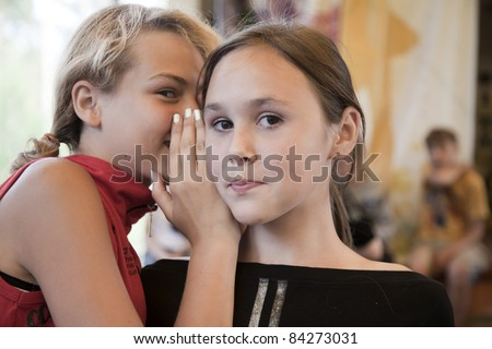 Young girl whispers something in another one's ear