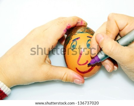 young girl who decorates an egg to kindergarten for the feast of Easter