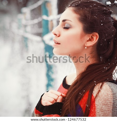 Young girl winter sensual portrait. Beautiful brunette poring outdoor in winter with closed eyes. - stock photo