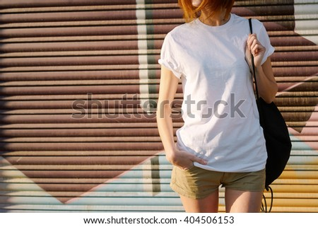 young girl with a backpack wearing a white blank t-shirt standing on a graffiti wall background