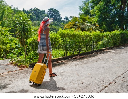Young girl with a bag goes on the road