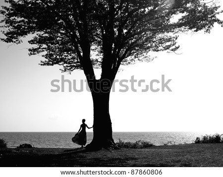 Young girl with a beautiful tree reflected in a puddle