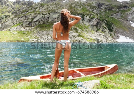 Young girl with a beautiful wooden canoe in the middle of nature, near a lake in Switzerland #674588986