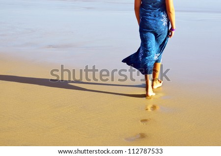 Young girl with a blue dress walking barefoot in the beach