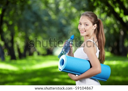 Young girl with a bottle of water and gym mat in the park