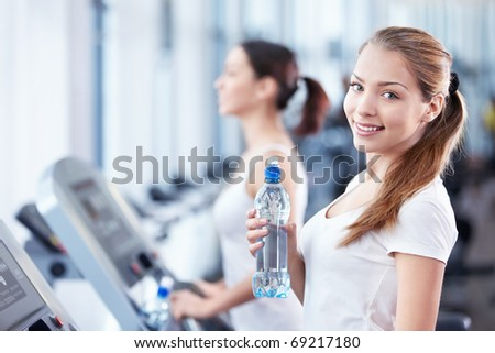 Young girl with a bottle of water on the treadmill