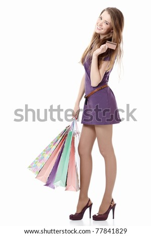 Young girl with a credit card and shopping bags on white background - stock photo