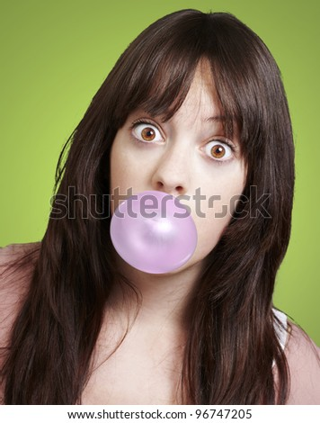 young girl with a pink bubble of chewing gum against a green background