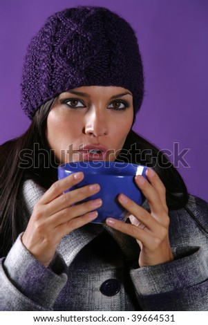 Young girl with a purple hat in a purple background drinking a cup of hot beverage.