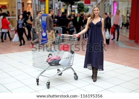 Young girl with a shopping trolley in supermarket