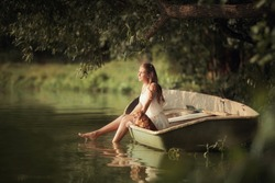 Young girl with a small dog in a boat on the lake in the rays of light
