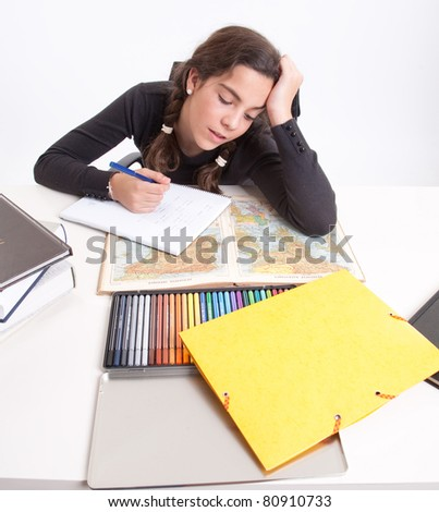 Young girl with a tired expression doing schoolwork