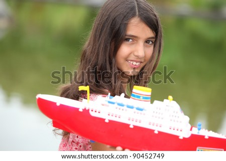 Young girl with a toy boat at a lake