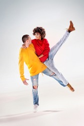 Young girl with afro dancing with boy, modern dancers.