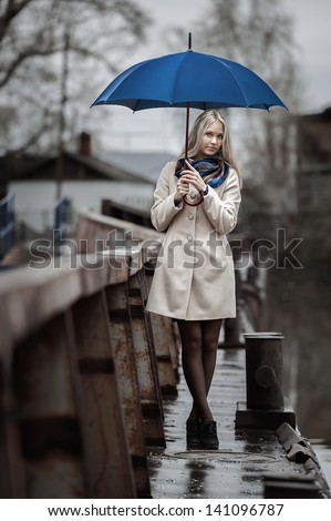 Young girl with an umbrella on a bridge in the rain