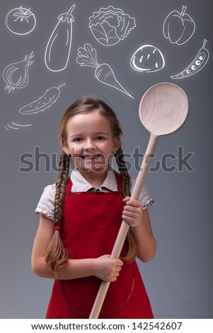 Young girl with apron, large wooden spoon and vegetables - healthy eating concept