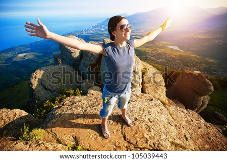 young girl with arms spread wide enjoys rise to the top of the mountain