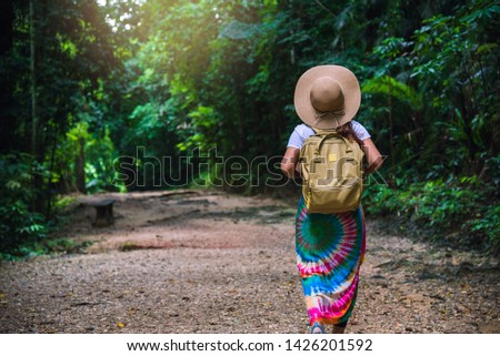 Young girl with backpack enjoying  travel nature in the forest Lush green trees. The back view of the girl who is walking travel in the forest. In the summer, Travel relax, Travel Thailand.