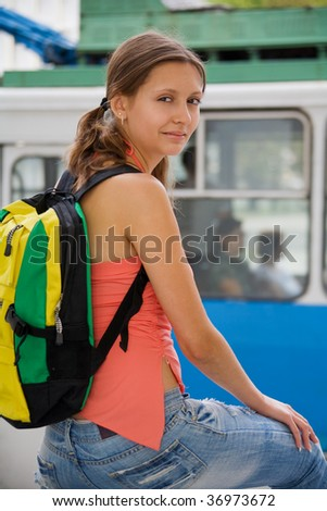 Young girl with backpack on city trolley bus background