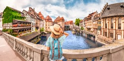Young girl with backpack standing on a bridge over d Ill river in Strasbourg, France