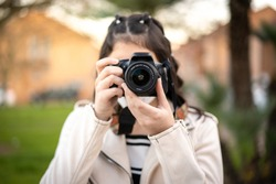 Young girl with black hair, Caucasian, dressed in beige windbreaker, black and white striped t-shirt, taking a picture with her reflex camera using a mask in a park