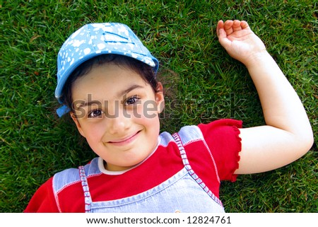 Young girl with blue hat laying in the grass smiling