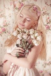 Young girl with bouquet from roses on background.