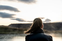 Young girl with brown hair in a ponytail gazing over a lake and a mountain into the sunset. Her hair blow in the wind and the sunlight contours the ponytail.