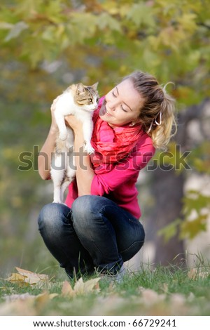 young girl with cat on natural background