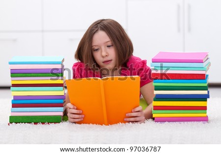 Young girl with colorful reading laying on the floor