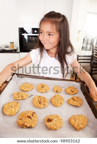 Young girl with cookie sheet filled with raw cookies