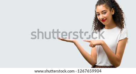 Young girl with curly hair holding copyspace imaginary on the palm to insert an ad on grey background #1267659904
