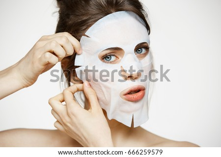 Young girl with facial mask looking at camera over white background. Cosmetic procedure. Beauty spa and cosmetology. - Shutterstock ID 666259579