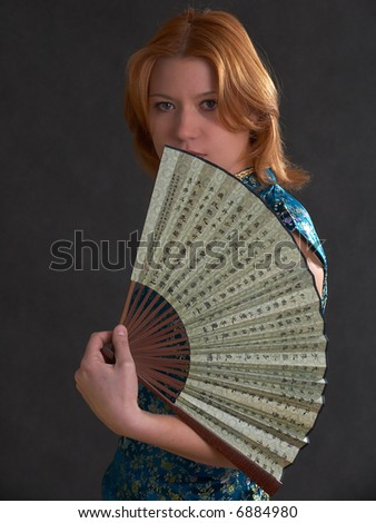 Young girl with fan isolated on the black background