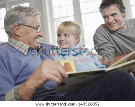 Young girl with father and grandfather reading story book at home
