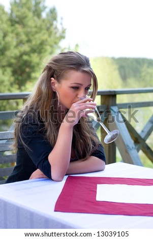 Young girl with glass of champagne on veranda