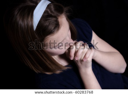 young girl with hands clasped in prayer